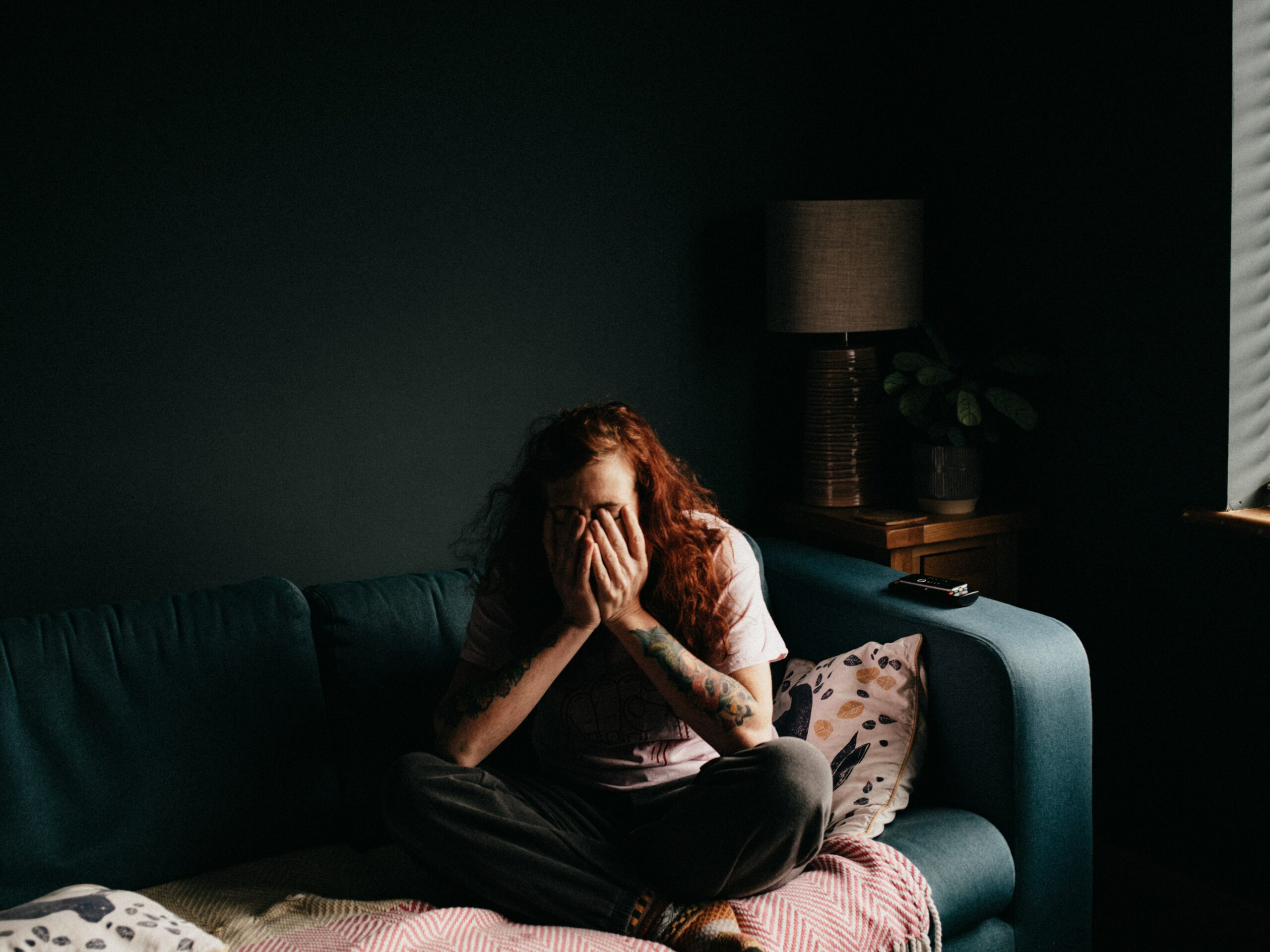 A person sitting on the couch in the dark with hands on their face
